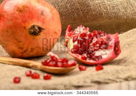 Ripe Juicy Pomegranate, Pomegranate Seeds In A Wooden Spoon And Pieces Of Pomegranate On A Backgroun