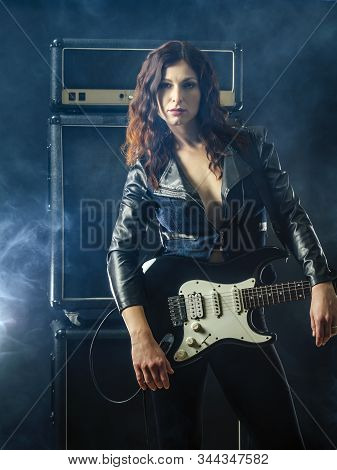 Young Beautiful Redhead Woman Playing An Electric Guitar In Front Of Large Amplifier.