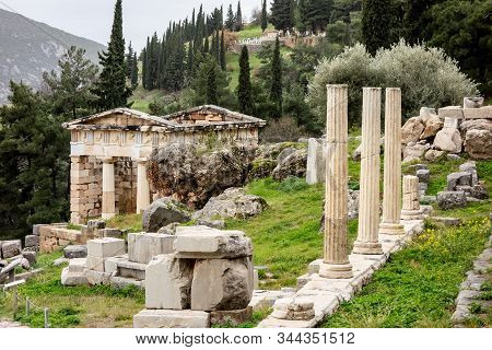 The Ancient Delphi City In Greece With Treasury Of Athenians And Historical Ruins Of Columns In Clou