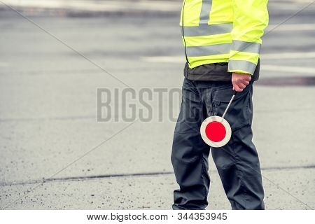Cop In Reflective Vest With Stop Sign. Police Road Patrol.