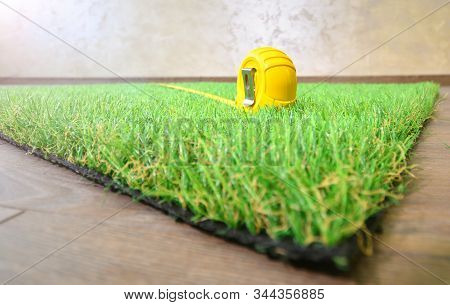 Artificial Grass And Measure Tape Lie On The Laminate Floor