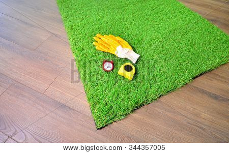 Artificial Grass On The Floor With Alarm Clock, Measure Tape, Protective Glooves. Quick Lawn Mowing