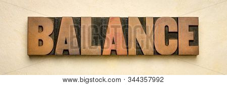 balance word in vintage wood type against handmade bark paper, harmony,  stability,  equilibrium and finance concept