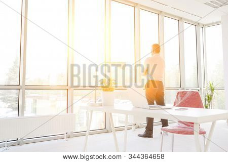 Mature thoughtful businessman in office with yellow lens flare