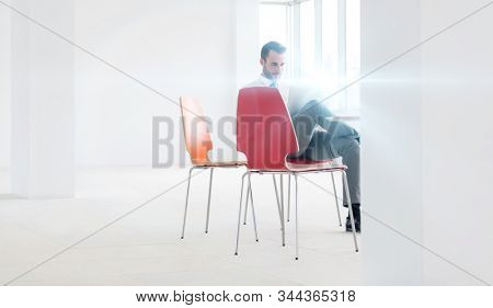 Businessman sitting while working on his laptop in new empty office