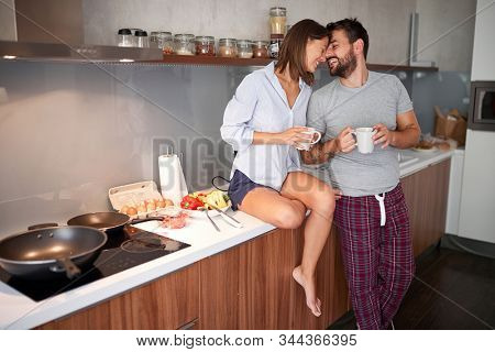 happy young  couple in morning celebratin valentines day in kitchen. sexy and in love