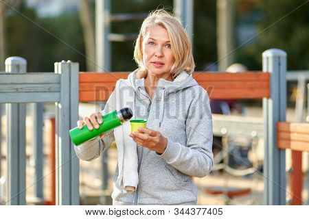 Elderly Woman Having A Drink After Doing Sports Outdoors.
