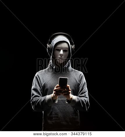 Computer Hacker In White Mask And Hoodie. Obscured Dark Face. Data Thief, Internet Fraud, Darknet An