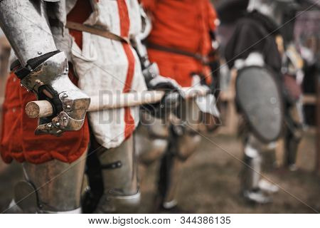 Side View Of Incognito Medieval Knight In Armor Holding Sword. Close Up Of Weapon In Hands Of Brave