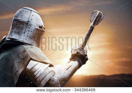 Side View Of Medieval Knight In Iron Armor Posing And Raising Big Sword. Close Up Portrait Of Brave