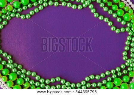 Mardi Gras Or Fat Tuesday Composition. Green Mardi Gras Beads On  Purple Background. Flat Lay, Copy