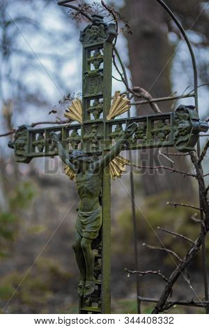 Old Weathered Metal Cross With Jesus Sculpture And Green Patina On A Graveyard