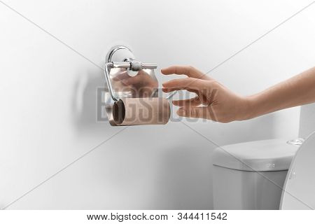 Woman Reaching For Empty Toilet Paper Roll In Bathroom, Closeup