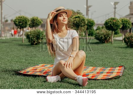 A Girl Is Sitting On The Blanket On The Grass In The Park With Crossed Legs. Her Eyes Are Closed And