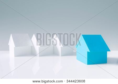 Searching for real estate property, house or new home, blue paper house standing out