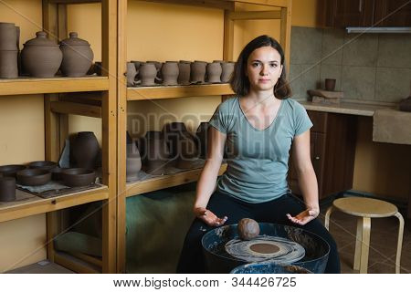 Woman Potter Sitting Near Wheel. Profession And Mastery Concept.