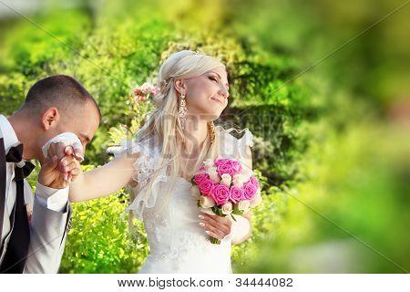 Groom Kissing Hand Of Female Bride, Outdoors Portrait