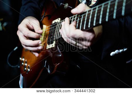 Guitarist Hands Plays Guitar Solo, Close-up. A Singer Man Playing Guitar.