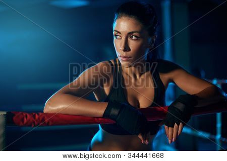 Front View Of Serious Young Professional Female Kickboxer Wearing Trendy Sports Outfit And Bandages
