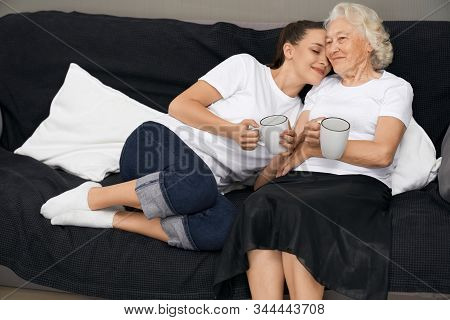 Front View Of Young Brunette Girl With Closed Eyes Lying On Shoulder Of Smiling Grandmother. Family