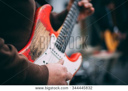 Close-up Of A Man Playing A Relic Electric Guitar In A Concert