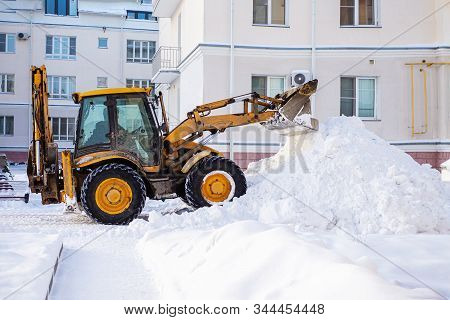 Snow Removal Equipment On The Road In Winter. Yellow Excavator Removes A Huge Mountain Of Snow. Clea
