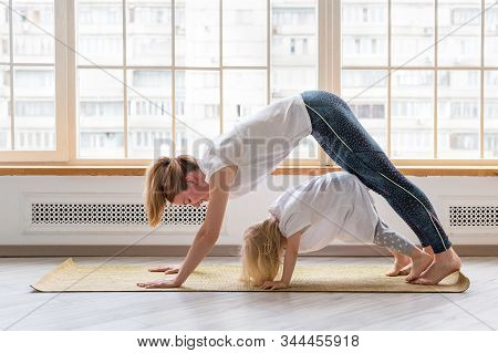 Young Mother Doing Yoga With 3-years Girl In Front Of Window. Downward Facing Dog Asana