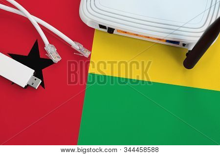 Guinea Bissau Flag Depicted On Table With Internet Rj45 Cable, Wireless Usb Wifi Adapter And Router.