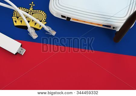 Liechtenstein Flag Depicted On Table With Internet Rj45 Cable, Wireless Usb Wifi Adapter And Router.