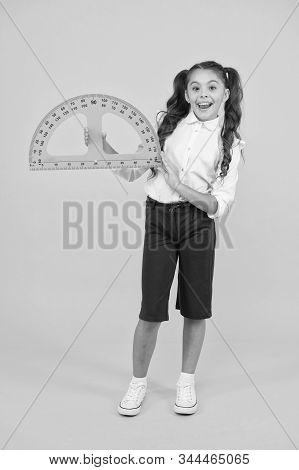 Schoolgirl Holding Protractor For Lesson. Little Child Preparing For Geometry. Adorable Small Girl U