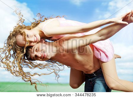 A Young Sexy Woman With Curly Hair In Shoty Dress And A Young Man With A Naked Torso Frolic Outdoor.