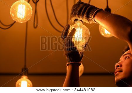 Asian Man / House Owner Cleaning Or Changing Vintage Light Bulb. House Maintenance Concept