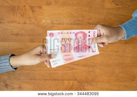 Lend Or Giving Money Concept. Top View Hand Giving Banknote Currency Chinese Yuan (cny Or Rmb) For P