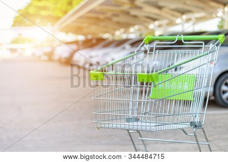 New Supermarket Trolley On The Street And Blur Of Car In Parking Lot