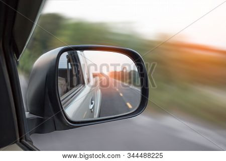 Cars Run Through The Street From The Gray Car's Side View Mirror.