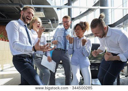 Five Happy Modern Business People Are Keeping Arms Raised And Expressing Joyful While Standing In La