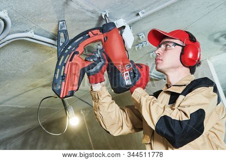 electrician service. Installer nailing tube holder for cable conduit