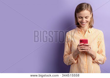 Portrait Of Beautiful Young Woman Looking At Screen Of Smartphone, While Chatting With Friend, Weari