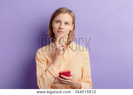 Thoughtful Caucasian Woman Stand Dreaming Or Thinking What To Write, Holding Mobile Phone In Hands,