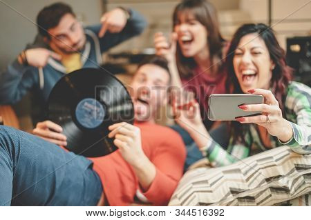 Happy friends taking selfie with mobile smartphone camera at home - Group young people having fun making hostel party - Youth millennial generation culture and technology lifestyle concept