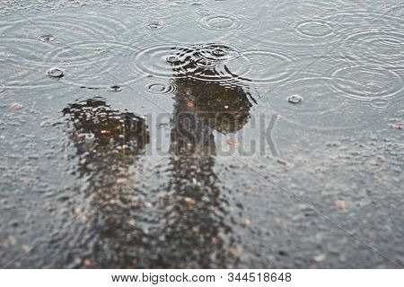 Reflection Of Two Rainboots In A Puddle At Rainy Day