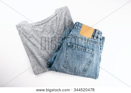 Gray Cotton T-shirt And Blue Jeans Flat Lay On White Background. Clothes In Minimal Style. Simple Vi