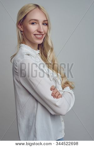 Young And Beautiful Long-haired Blond Woman In White Blouse Standing With Her Arms Folded And Lookin