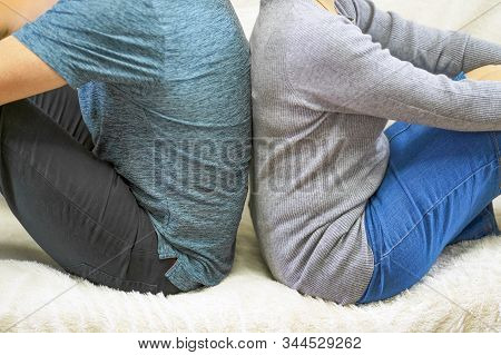 Couple With Their Backs Turned To Each Other Sitting On White Couch. ?ngry And Upset Couple Turning
