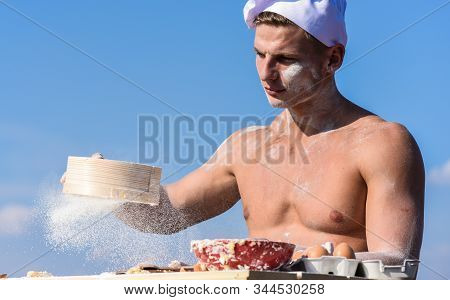 Man Muscular Baker Or Cook Sifts Flour Through Sieve. Baker Working With Flour And Sieve, Kneading D