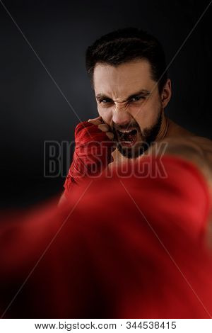 Sportsman Boxer Throwing A Fierce And Powerful Punch Forward In The Camera. Muscular Man On Black Ba