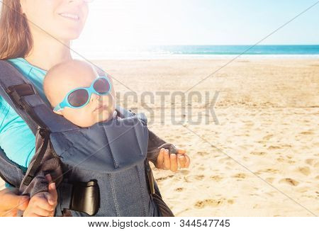 Mother And Infant Baby In Carrier On The Sea Beach