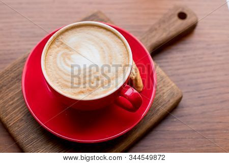 Coffee-break. Red Cup Of Cappuccino With Beautiful Latte Art On Old Wooden Background. Latte Art Cof