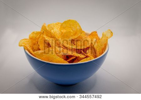 A Blue Bowl Filled With Crispy And Spicey Chips