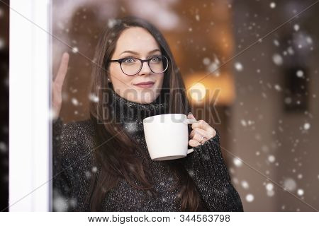 Woman Relaxing By The Window And Drinking Tea
